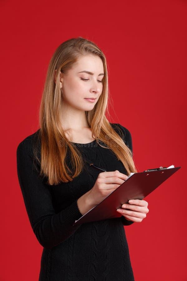 Een ernstig meisje schrijft in een klembordholding het in haar handen stock foto