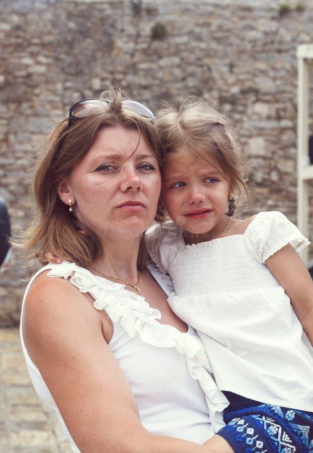 Een ernstige en strikte moeder houdt een gealarmeerd meisje die t onderzoeken stock foto's