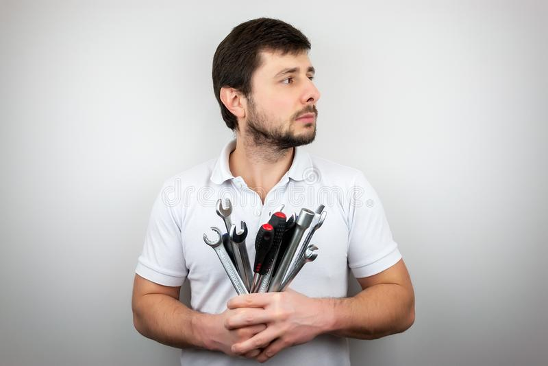 Een ernstige gebaarde mens in een witte t-shirt met een boeket van moersleutels en schroevedraaiers die aan de kant kijken royalty-vrije stock fotografie