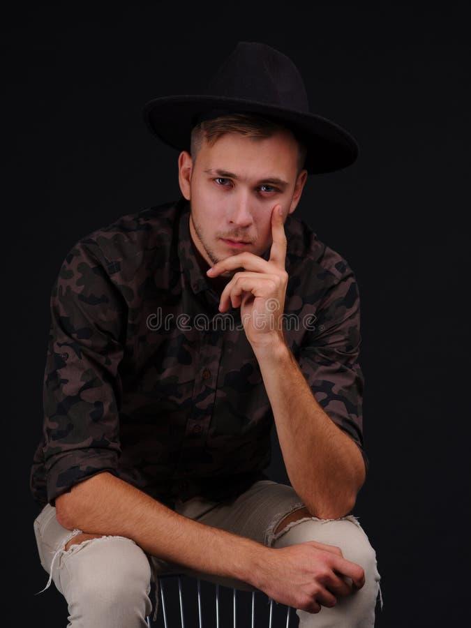 Een ernstige kameraad in een hoed zit op een stoel met een peinzende blik en houdt een hand aan zijn gezicht stock foto's