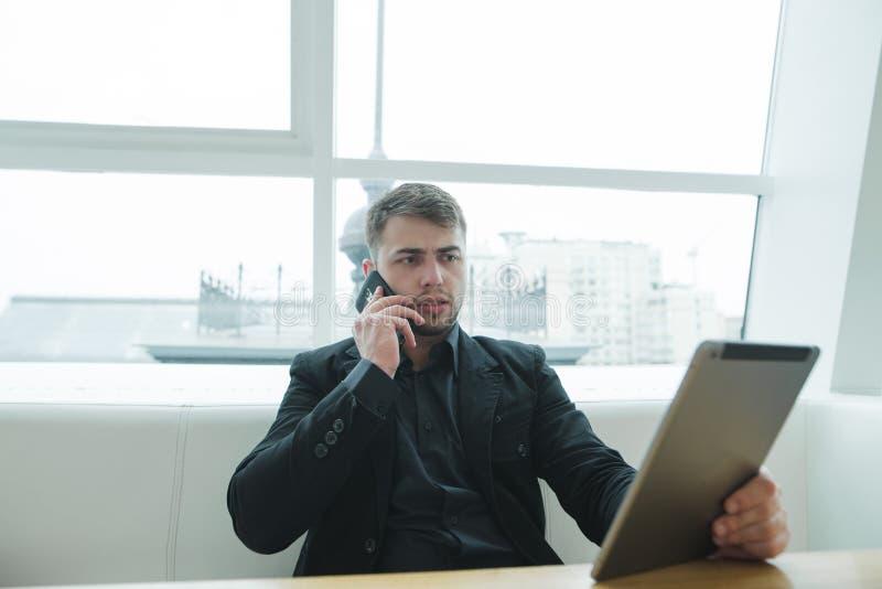 Een ernstige mens bekijkt de tablet en spreekt telefonisch in een koffie voor een kop van koffie Een zakenman geniet van gadgets stock foto's