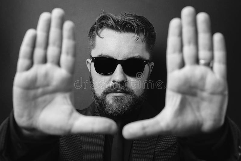 Een ernstige mens met een baard en een modieus kapsel voert het ontwerpen met zijn handen uit Geleid in een bedrijfs zwart kostuu stock afbeeldingen