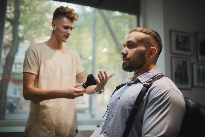 Een ernstige mensen bezoekende herenkapper in een herenkapper Een kapper die hulpmiddelen voor een scheerbeurt op een salonachter stock fotografie