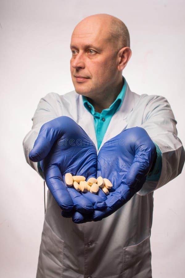 Een ervaren arts die van de jaren '50, een witte laag, in blauwe rubberhandschoenen draagt en het glimlachen, biedt gele pillen a stock afbeelding