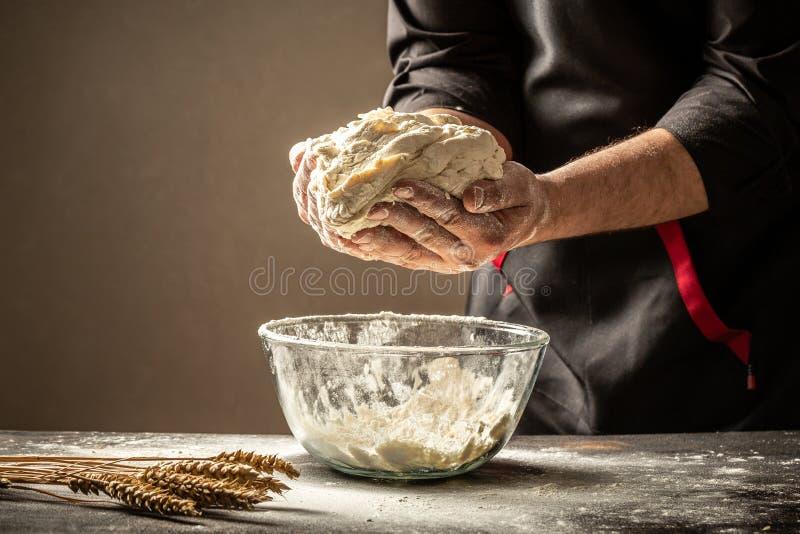 Een ervaren chef-kok in een professionele keuken bereidt het deeg met bloem voor om de bio Italiaanse deegwaren te maken het conc stock foto