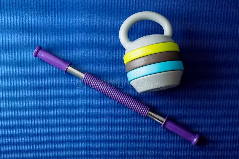 Een expander en een regelbare kettlebell op de blauwe achtergrond van de yogamat stock fotografie