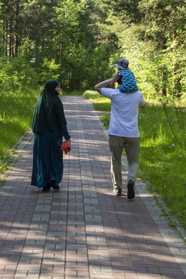 Een familie loopt in het park - een vrouw in een hijab, een man die een kind op zijn schouders vervoeren Achter mening stock foto