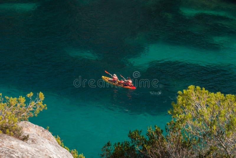 Een familie op een kajak in het overzees van inham Macarelleta in Menorca royalty-vrije stock afbeelding