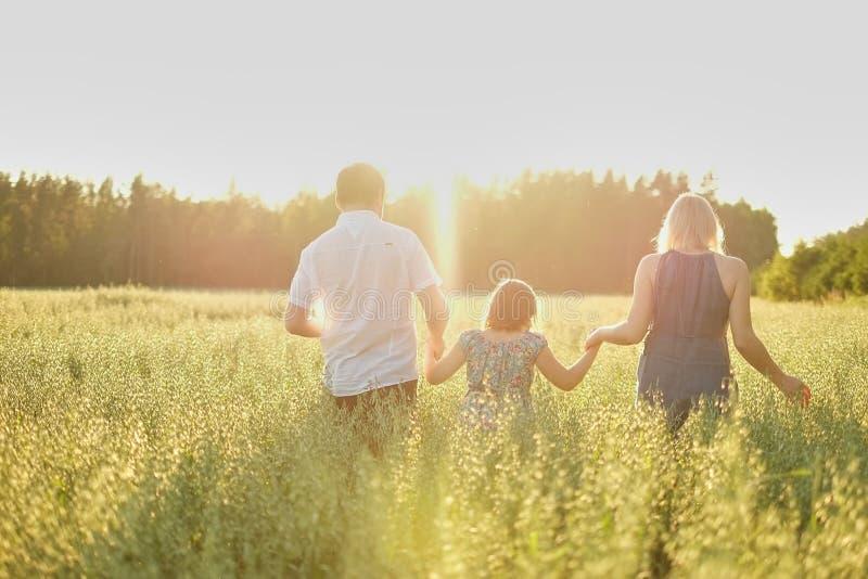 Een familie van drie met een dochter loopt over het gebied die naar de het plaatsen zon, handen houden blur Achtergrond stock fotografie