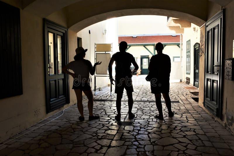 Een familie van drie reizigers die schaduw in een steeg in een historische stad van Eger, Hongarije zoeken royalty-vrije stock foto
