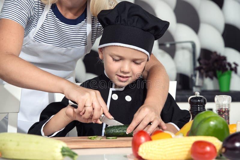 Een familie van koks Het gezonde Eten De moeder en de kinderen bereiden plantaardige salade in keuken voor royalty-vrije stock foto's