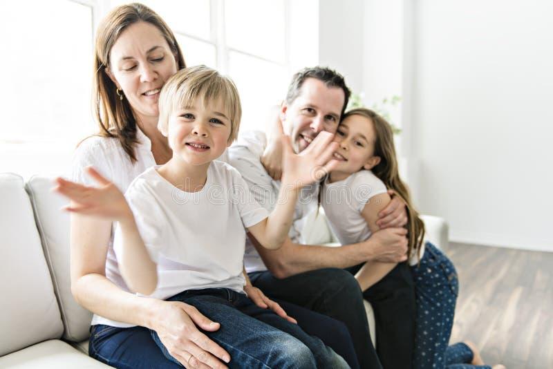 Een Familie van vier die pret op de bank hebben thuis stock foto's