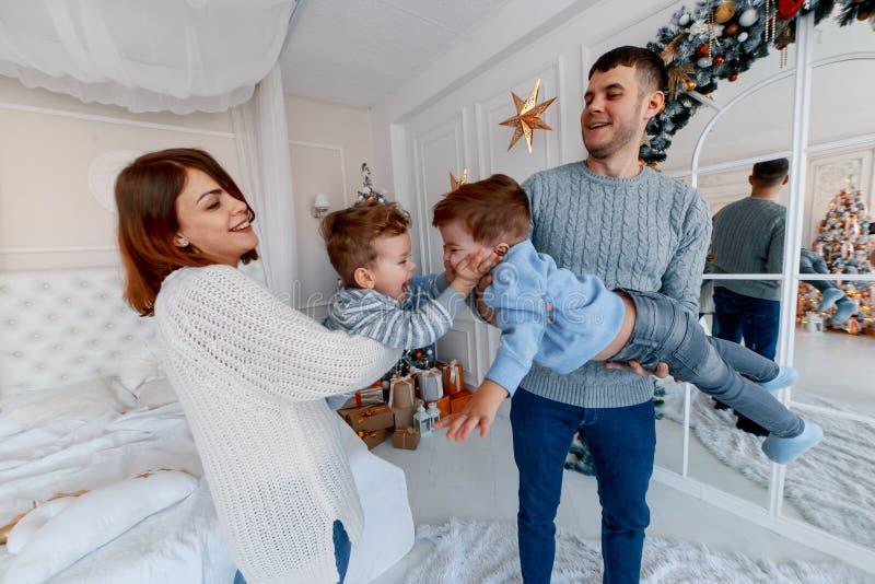 Een familie van vier die voor de Kerstmisboom koesteren liefde, geluk en groot familieconcept royalty-vrije stock foto's