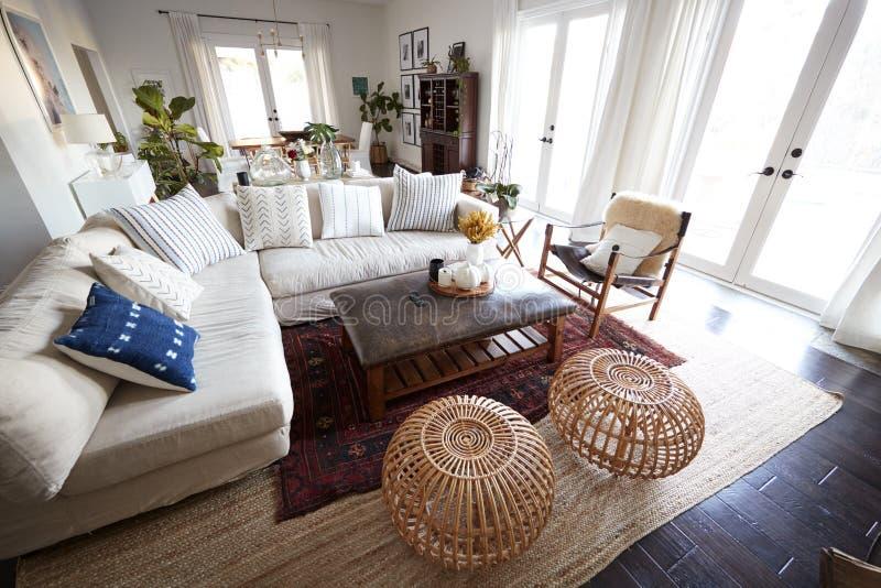 Een familiewoonkamer met Franse vensters en een grote comfortabele die hoekbank, in daglicht wordt gezien, bijkomende mensen in s stock foto's