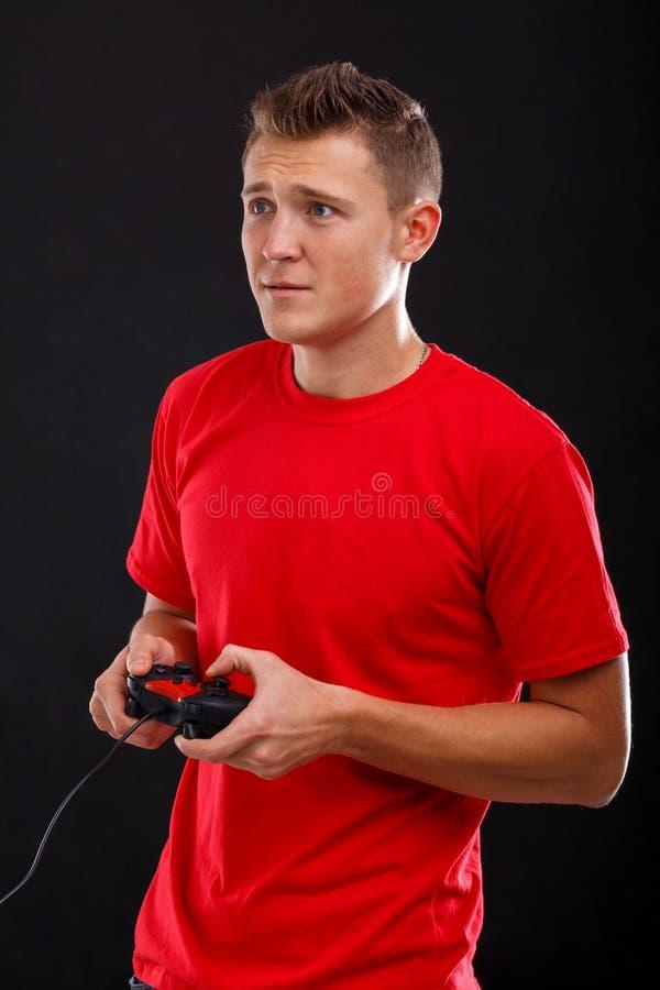 Een fascinerende jonge kerel met rente het spelen in de consoleholding met een spelbedieningshendel Zwarte achtergrond royalty-vrije stock afbeelding