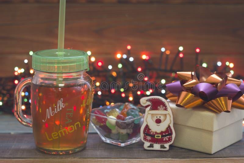 Een feestelijk stilleven met een glaskop thee met een GLB, een giftbox, een kom van suikergoed een stuk speelgoed santa en feelic stock fotografie
