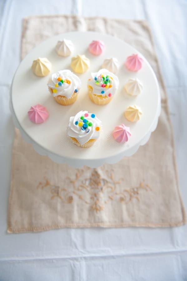 Een feestelijke vertoning van cupcakes met bestrooit en suikerachtige schuimgebakjebeten in pastelkleuren stock fotografie