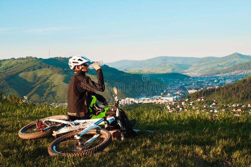 Een fietser op een bergfiets neemt bergop toe En bekijkt het toneellandschap stock afbeelding