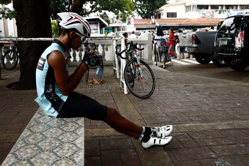 Een fietser rust en zit op een parkbank terwijl het gebruiken van zijn smartphone royalty-vrije stock afbeelding