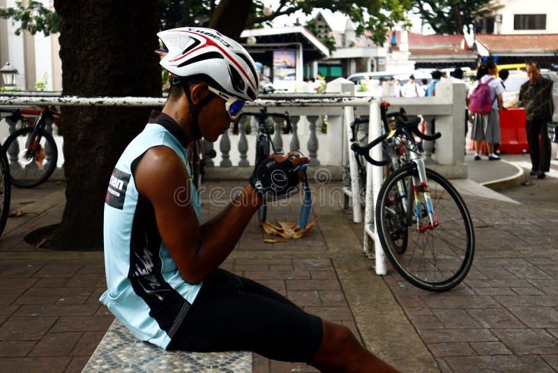 Een fietser rust en zit op een parkbank terwijl het gebruiken van zijn smartphone stock afbeelding
