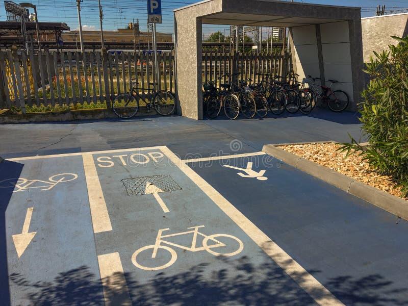 Een fietsweg en een voetstraat, en fietsenrekken op een voetgebied met vele geparkeerde fietsen stock afbeeldingen