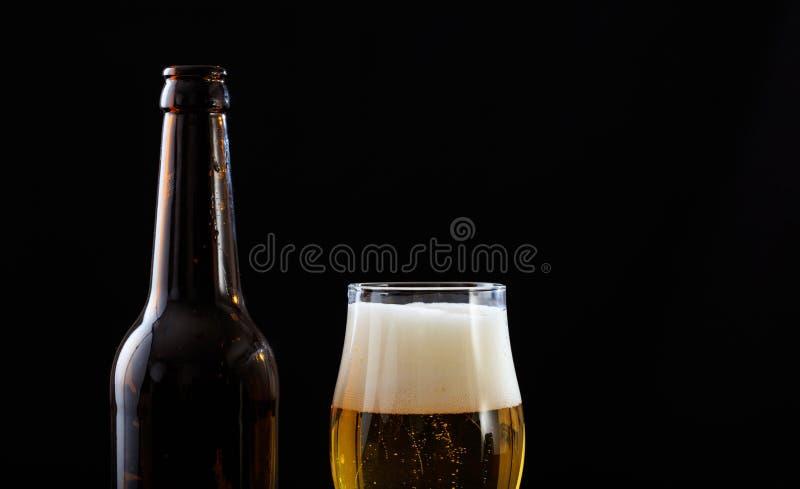 Een fles en een glas van bierclose-up, zwarte achtergrond stock fotografie