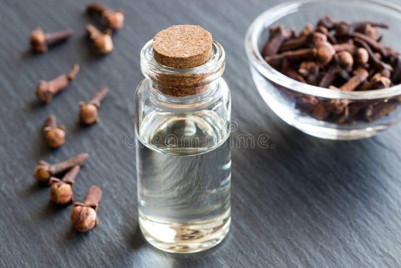 Een fles kruidnageletherische olie met droge kruidnagels royalty-vrije stock afbeelding