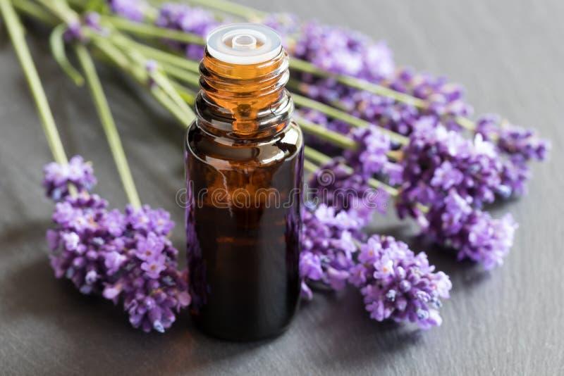 Een fles lavendeletherische olie op een donkere achtergrond stock afbeeldingen
