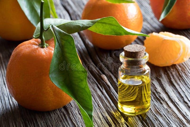 Een fles mandarijnetherische olie met mandarijnen in backg royalty-vrije stock afbeeldingen