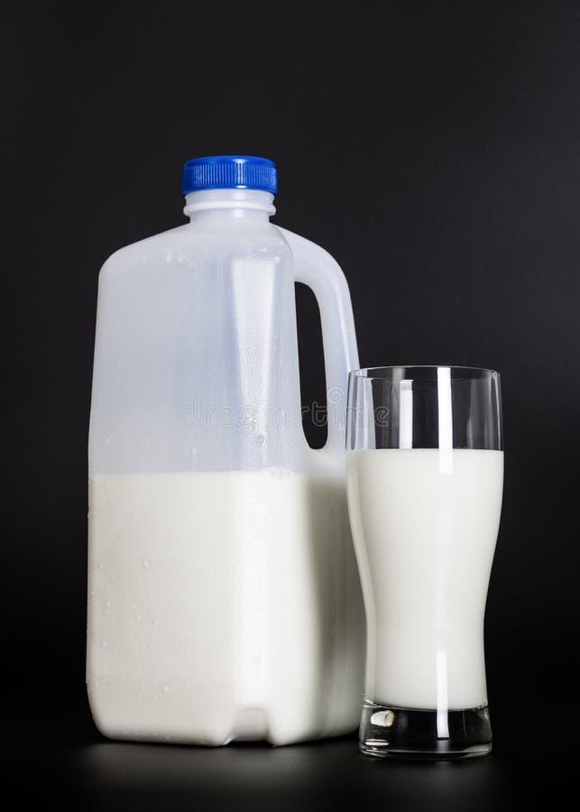 Een fles melk en glas op een donkere achtergrond royalty-vrije stock foto's