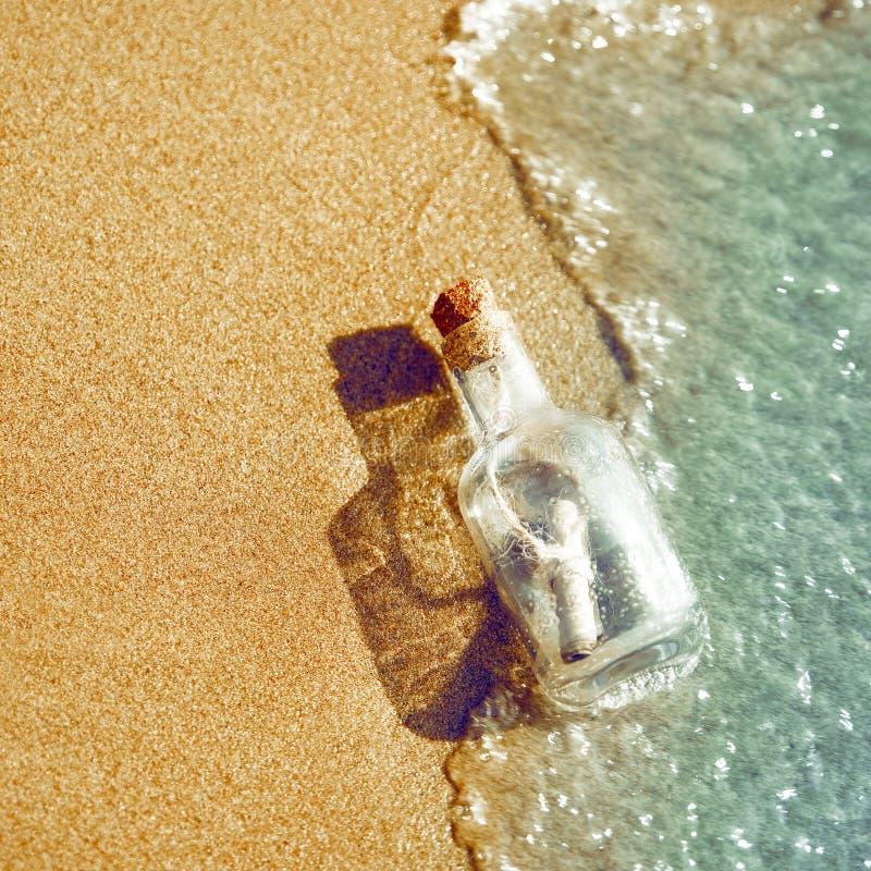 Een fles met een bericht wordt geworpen door een golf op een zandig strand Het concept hoop de fles drijft in de brandingslijn stock foto's