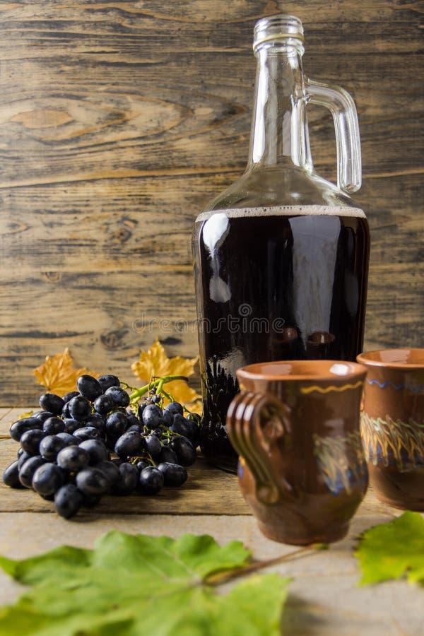 Een fles rode wijn dichtbij druiven en ceramische mokken op houten rustieke achtergrond royalty-vrije stock foto