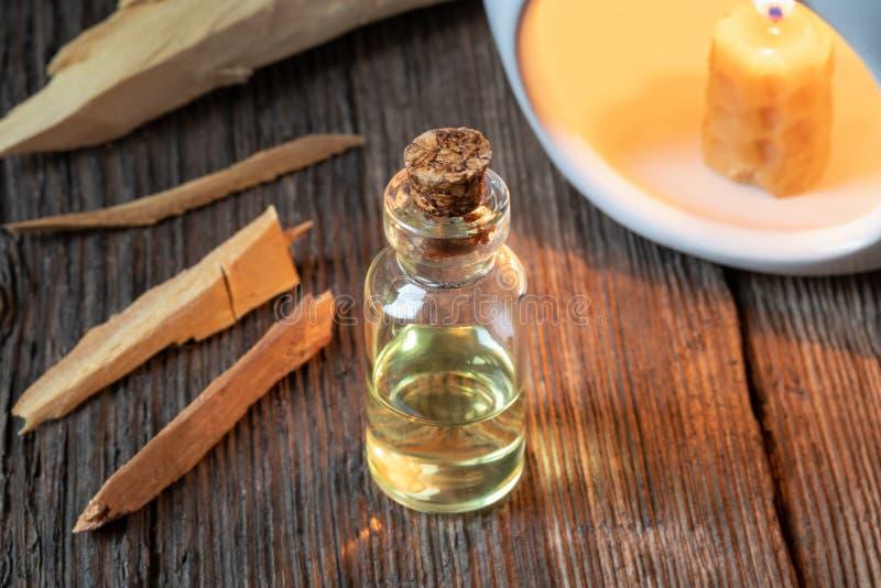 Een fles sandelhoutetherische olie met wit sandelhout stock afbeelding