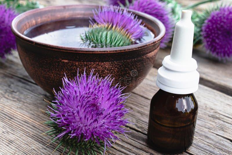 Een fles tint of de etherische olie van het drankje en bloemen van distel op een houten achtergrond royalty-vrije stock afbeelding