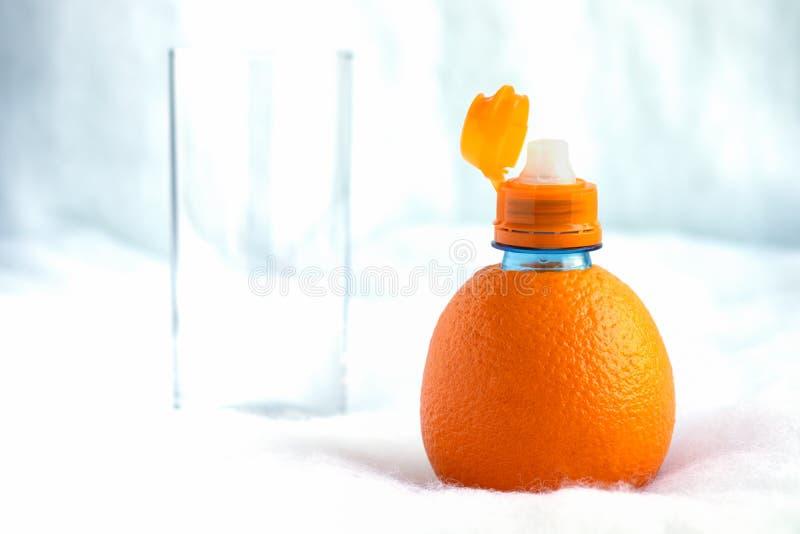 Een fles van natuurlijke sinaasappel met een open hals wordt gemaakt is bereid om vers sap in een lang glas te gieten dat stock afbeeldingen