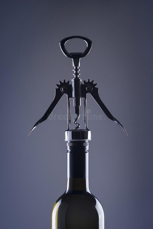 Een fles wijn met een modieuze kurketrekker voor het openen stock fotografie