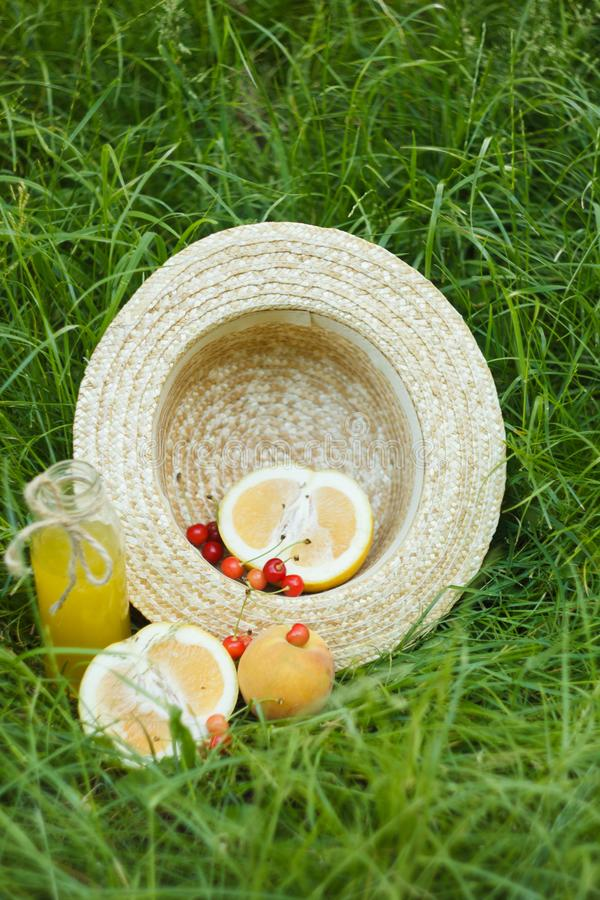 Een flessenfles eigengemaakt limonadesap met kers en citrusvruchten met strohoed die op het gras in openlucht liggen Picknick  stock foto