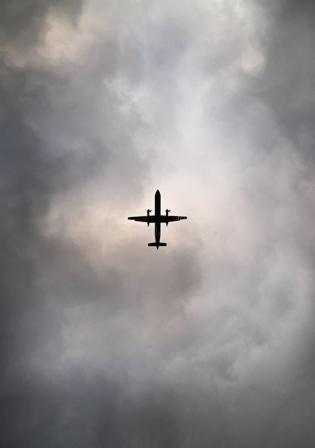 Een forenzenvliegtuig tegen bewolkte hemel wordt gesilhouetteerd die stock afbeeldingen
