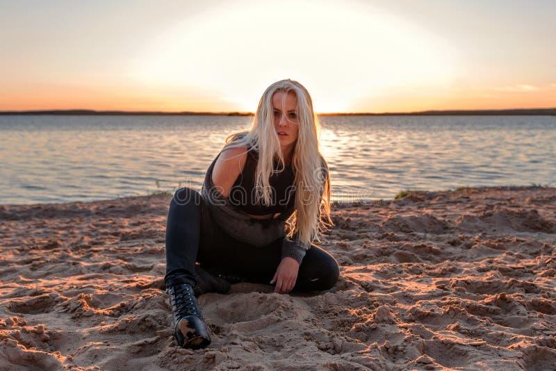 Een formidabel donker blondemeisje zit op het zand op een strand in donkere kleren met een starende blik bij de avondzonsondergan royalty-vrije stock foto