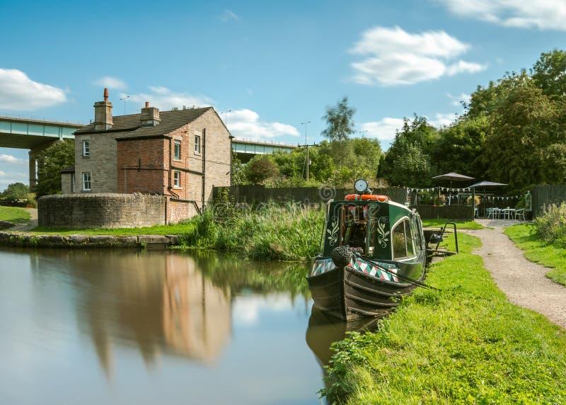Een foto die een omgezet kanaal documenteren narrowboat doet dienst als tearoom met een klein openluchtgebied van de tuinplaatsin royalty-vrije stock afbeelding