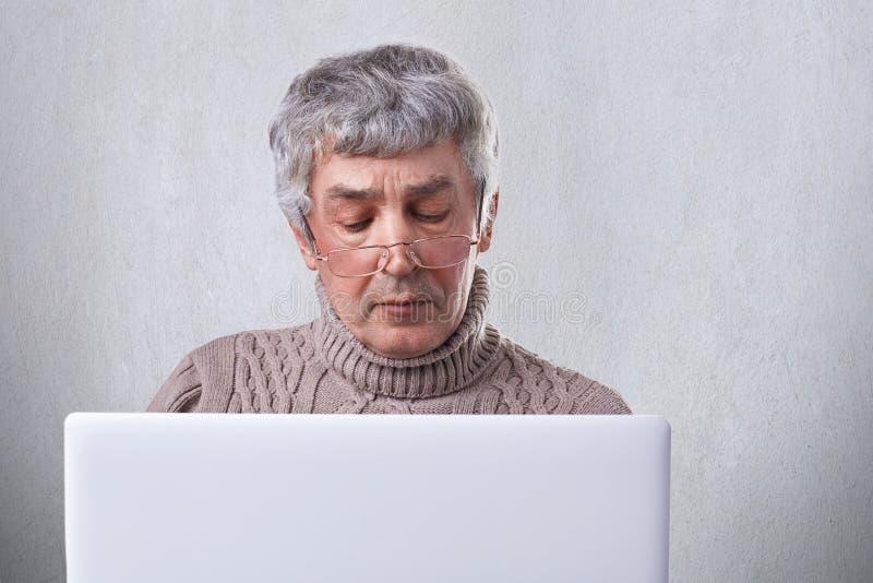 Een foto van de hogere mens met grijs haar en rimpels concentreerde zich op het scherm van zijn laptop Peinzende rijpe mens in oo stock foto's