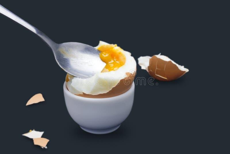 Een foto van gekookt ineenstorting gebroken kippen beige ei en een lepel met dooier op donkerblauw Foto van de ei` s de vloeibare stock fotografie