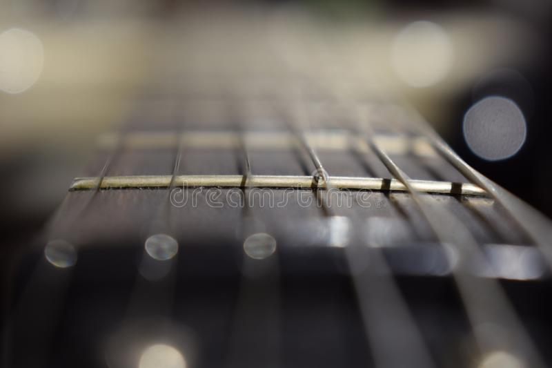 Een foto van een gitaarhals met koorden en een houten textuur - het materiaal van een gitaarhals Selectieve nadruk op één gitaard royalty-vrije stock afbeeldingen