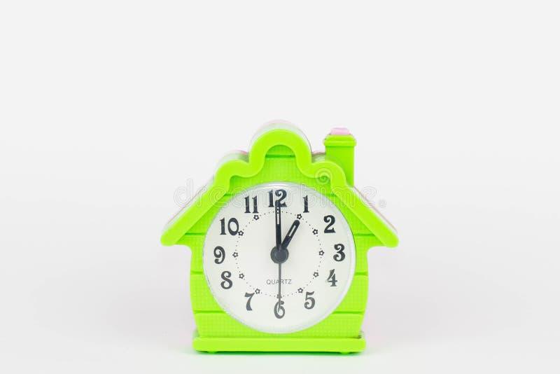 Een foto van een mini groen wekkerhuis met een tijd die op 1 klok van o richten ` stock afbeelding