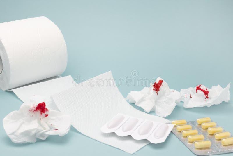 Een foto van pillen, de gebruikte bloedige toiletpapierbladen, de rectale kaarsen en een tioletdocument rollen Hemorroïden, hea v royalty-vrije stock foto's