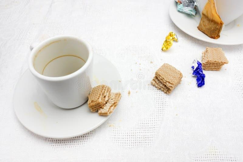 Een foto van vuile koppen, gebruikt theezakje, de omslag van het chocoladesuikergoed en droge chocoladewafels verkruimelt resten  stock afbeeldingen