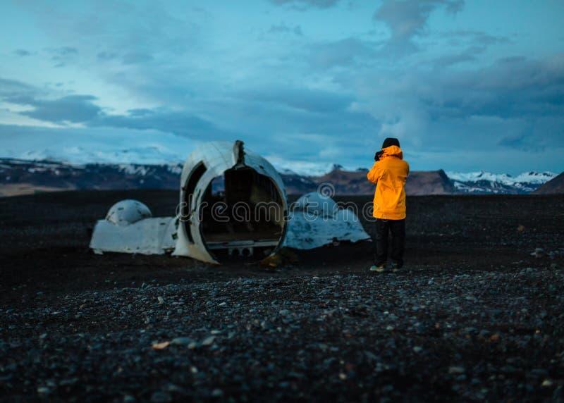 Een fotograaf in een gele regenjas die een beeld van een oud gebroken vliegtuigdeel nemen stock illustratie