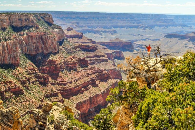 Een Fotograaf Sets Up For een Beeld op een Vlakke Rand in Grand Canyon van Arizona stock fotografie