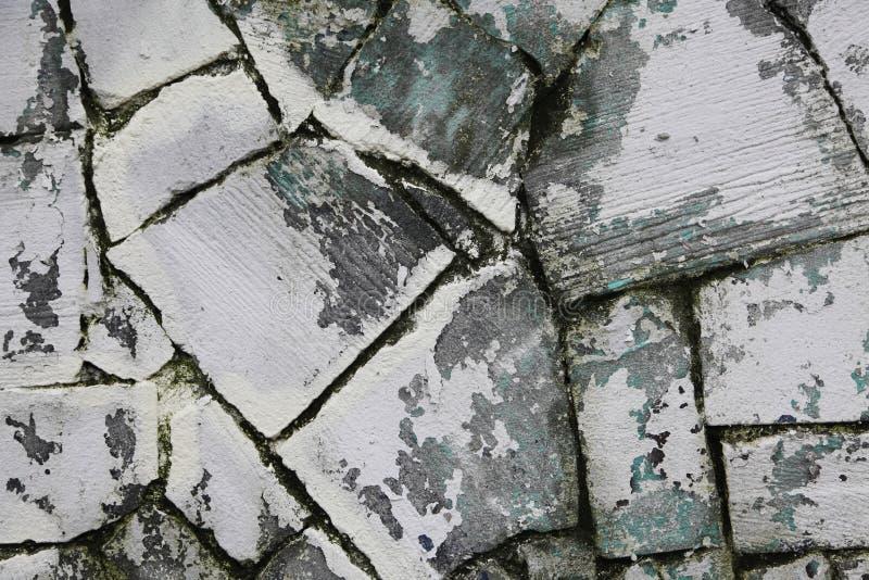 Een fragment van de oude muur van gezaagd natuursteen grijs Zandsteen met sporen van vergoelijkt het wit van de schilkalk stock afbeelding