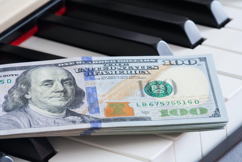 Een fragment van honderd dollarsrekeningen op pianosleutels stock foto's